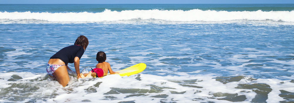 Kleiner Junge auf dem Surfbrett liegend mit seinem Au-pair im Wasser