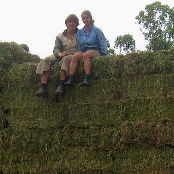 Work and Travel Teilnehmer Maria und Simon auf einem Stapel Heuballen