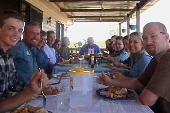 Gruppe von Teilnehmern sitzt beim gemeinsamen Lunch auf der Veranda