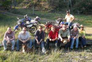 Eine Gruppe Work and Travel Teilnehmer sitzt auf einem Baumstamm